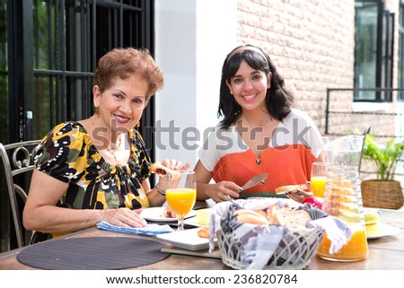 A senior hispanic woman having breakfast outdoors with a daughter. Outdoor dining in summer. Focus on senior woman. - stock photo