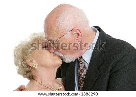 A senior husband and wife locked in a romantic kiss. - stock photo