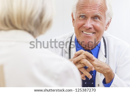 A senior male doctor sitting at a desk in an office wearing a shirt, tie and stethoscope talking to elderly female patient.
