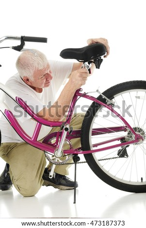 A senior man adjusting his granddaughter's bicycle seat.  On a white background.