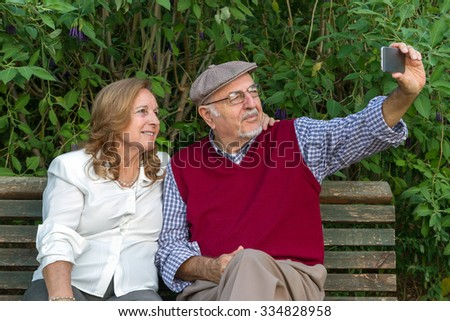 A senior man and woman hand using a touchscreen cell phone - stock photo