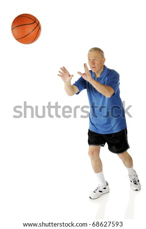 A senior man attempting to shoot a basketball into the basket.  Ball with some motion blur.  Isolated on white. - stock photo