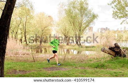 A senior man dressed in black and green is running close to the lake during a fresh spring day - stock photo
