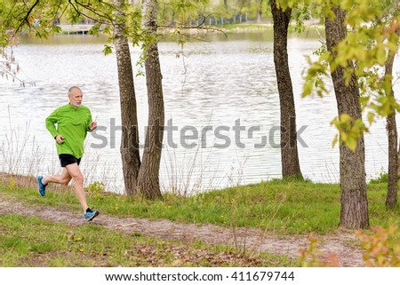 A senior man dressed in black and green is running in the park, close to the lake, during a gray spring day - stock photo