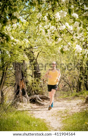 A senior man dressed in black and yellow is running in the forest, close to the lake, under an apple blossom, during a warm spring day - stock photo