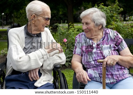 A senior man giving his senior wife of many years a small pink rose as a token of his love to her after all these years. - stock photo