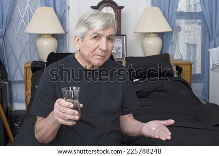 A senior  man holds a glass of water with a pill. - stock photo