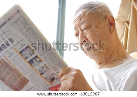 a senior man is reading newspaper - stock photo