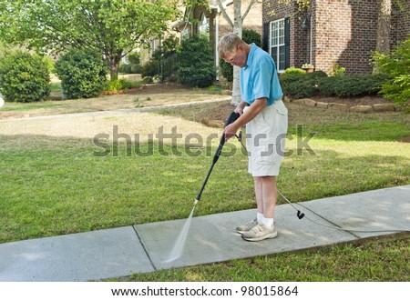 A senior man pressure washing the walkway to his home. - stock photo