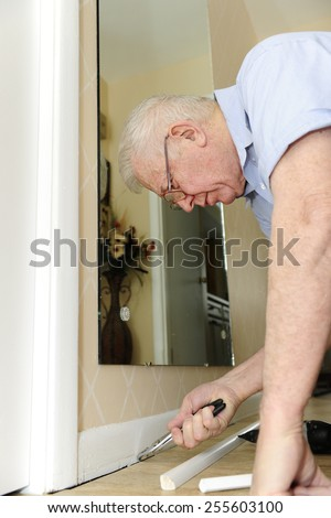 A senior man pulling nails from his baseboard as he upgrades his home.  - stock photo