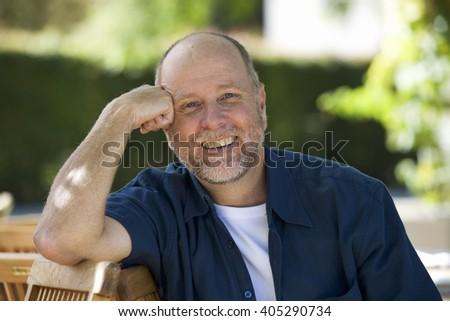 A senior man sitting in a garden - stock photo