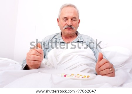 A senior man sitting in bed, eating drugs with knife and fork.