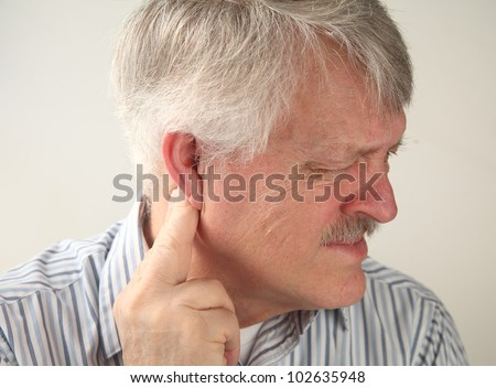 a senior man suffers from pressure behind his ear - stock photo
