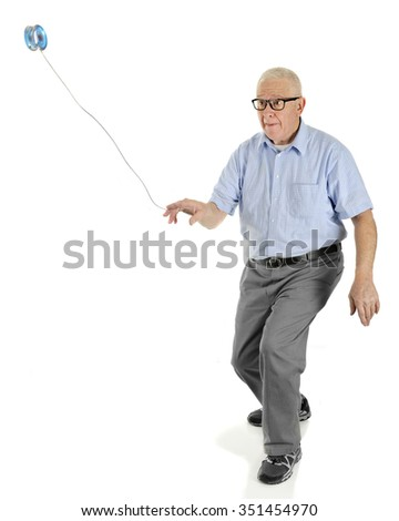 "A senior man throwing out his yo-yo as he begins the ""around the world"" maneuver.  On a white background. - stock photo"