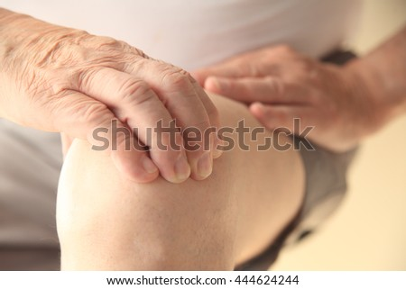 A senior man with a painful knee joint - stock photo