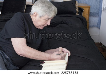 A senior man writes while resting on his bed. - stock photo
