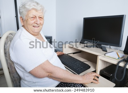 A senior person in front of his computer - stock photo