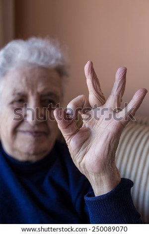 a senior person making okay sign with fingers - stock photo