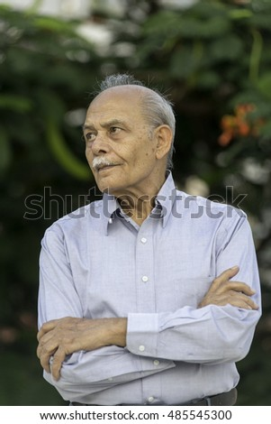 A senior South Asian man in his 70s or 80s looking off camera