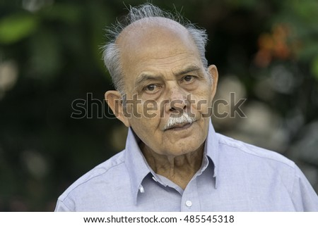A senior South Asian man in his 70s or 80s looking to camera