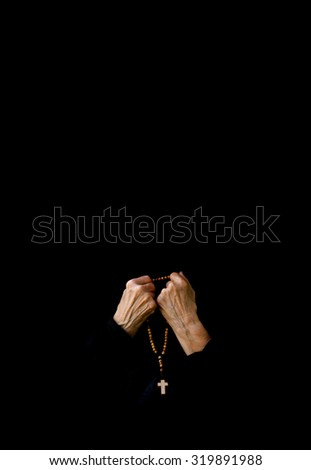 A senior woman between 70 and 80 years old, dressed in black is praying in the garden. Fron view - stock photo