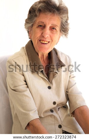 A senior woman between 70 and 80 years old expresses her happiness while sitting. - stock photo