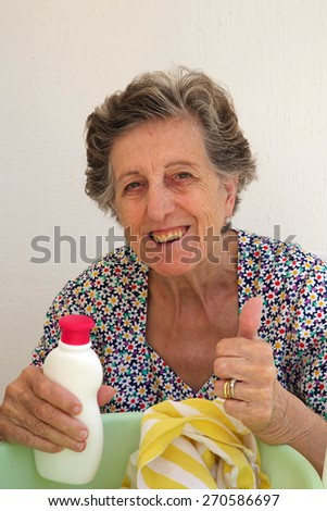 A senior woman between 70 and 80 years old is showing that she found a good liquid detergent for washing the cloths by hand.