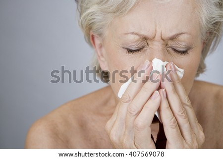 A senior woman blowing her nose - stock photo