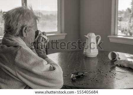 A senior woman calmly drinking coffee after murdering her partner after having endured years of abuse - stock photo