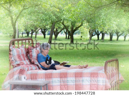 A senior woman enjoys quiet pleasure reading with her dog as she relaxes on an old-fashioned bed placed at the edge of a walnut grove as a private summer retreat. - stock photo