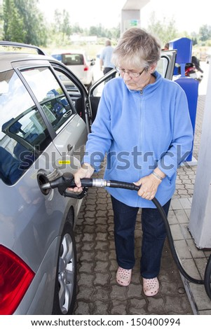 A senior woman filling up a car with diesel - stock photo