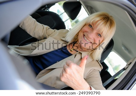 A senior woman happy at the wheel of her car.