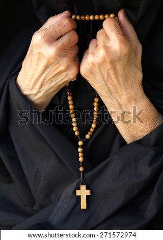 A senior woman  in black dress is praying. Front view - stock photo