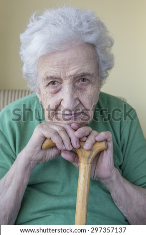 a senior woman leaning on cane