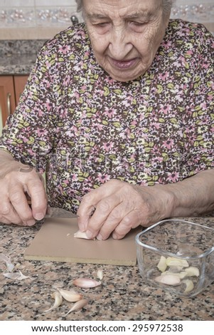 a senior woman peeling garlic in kitchen  - stock photo
