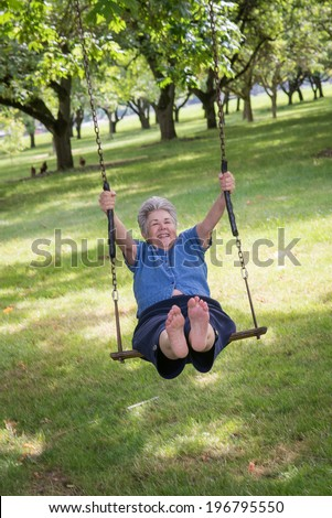 A senior woman relives her childhood memories as she joyfully swings on a rustic swing at the edge of a country walnut orchard. - stock photo