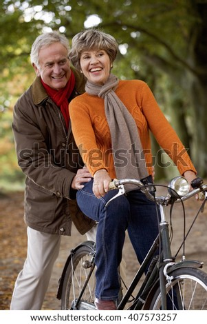 A senior woman riding a bike with her partner pushing her along