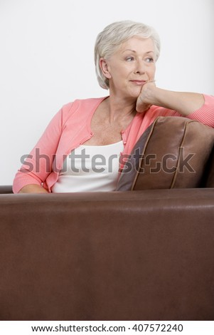 A senior woman sitting on a sofa - stock photo