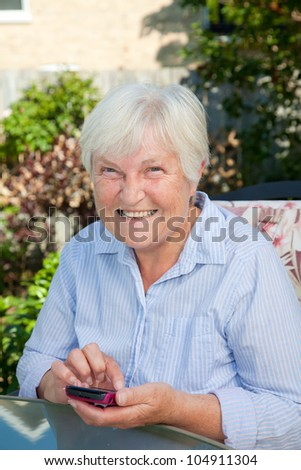 A senior woman smiling as she works with her smartphone.