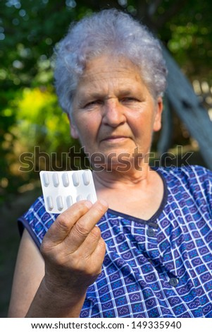 A senior woman with pills in her hand - stock photo