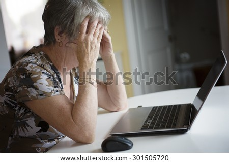 A senior woman working on her laptop in her kitchen table - stock photo