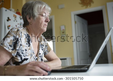 A senior woman working on her laptop in her kitchen table