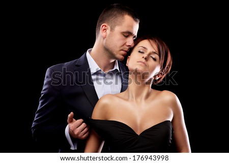 A sensual picture of a young couple flirting over black background