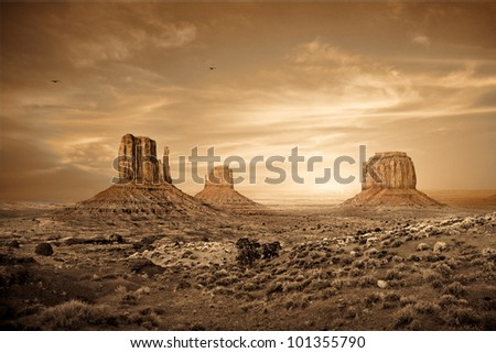 A sepia toned photograph of a sunset in the Monument Valley region of the Colorado Plateau that spans the northern border of Arizona and southern border of Utah.