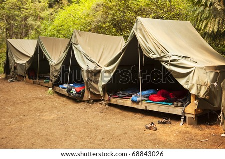 A series of basic canvas tents on wooden tent platforms at a Boy Scout camp provide the basics for shelter and not much more.