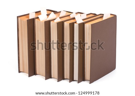 A series of books with bookmarks stand upright isolated on white background