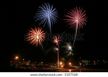 A series of fireworks exploding over the ocean an a beachside city - stock photo