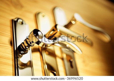 A series of golden handles on a wooden board
