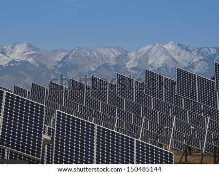 A series of large solar panels forms a symmetrical line at a power plant in the San Luis Valley of central Colorado. - stock photo
