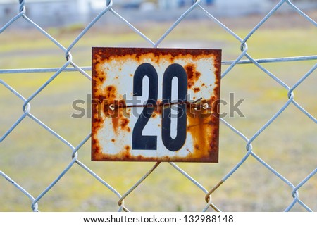 A series of rusted old signs or tags are attached to this chain link fence with orange and white rust and the numbers clearly visible. - stock photo